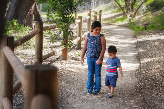 Older sister holding little brothers hand while walking in a wooded pathway in a California national park.