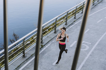 From above view through fence of young lady in sportswear running on quay near water in city