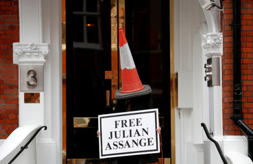 A demonstrator wearing a traffic cone on a head holds a banner outside Ecuador's embassy, where WikiLeaks founder Julian Assange is staying, in London