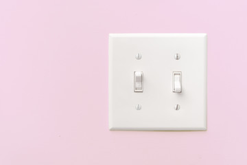 Interior light switch on pink wall with copy space.