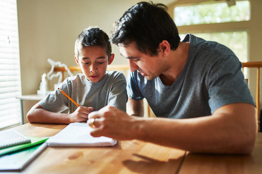 father helping son with homework on table at home