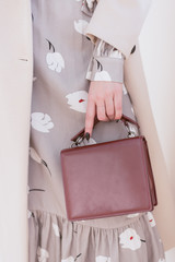 burgundy bag in hand. Vertical photo of a girl in a gray dress and a beige coat. without face