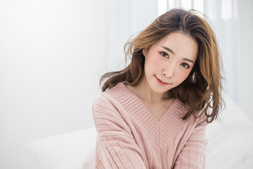 Portrait of young beautiful sexy asian woman relax in her bedroom. Smile happy asian girl isolated on white background. Beauty old winter relax freedom lifestyle concept