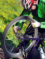 Closeup picture of a cyclist fixing breaks on his bicycle wheel against spring park background