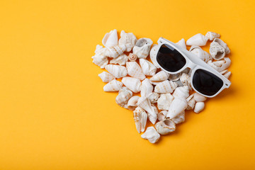 Heart from seashells on orange background. Love summer. Sea holidays. Hot sunny background