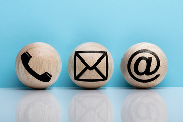 Three Wooden Ball With Contact Icon Against Blue Background