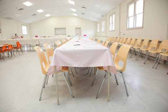 long table with white tablecloth and yellow chairs in a large fire hall or legion