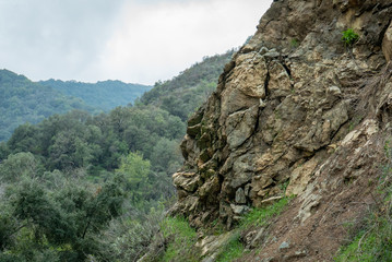 Looking past a rocky outcropping over a tree-covered hills on mountains in Southern California