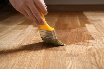 Obraz Home renovation parquet. Varnish paintbrush strokes on a wooden parquet - fototapety do salonu