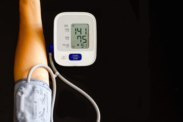 Woman take care for health,using sphygmomanometer to measure blood pressure,pulse and heart rate by self,isolated on dark background. Healthcare and hypertension concept.
