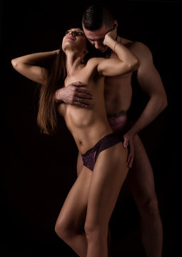muscular naked man and sexy woman hugging on a dark background, sexual foreplay of a young couple