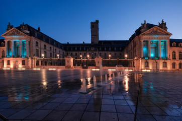 Palace of the Dukes of Burgundy at the hour of dawn. City of Dijon. France. In the foreground there is a fortan. The light of street lamps reflected on the wet pavement. Wall mural