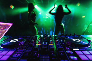 DJ mixer in a nightclub with dancing on the background of go-go dance girls