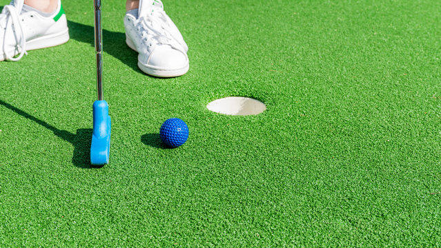 Close up of a club prepares to hit a ball during a mini golf game.