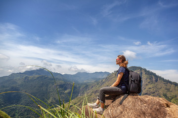 Happy young beautiful girl tourist with a backpack. Sit in the mountains and enjoy the view and nature.