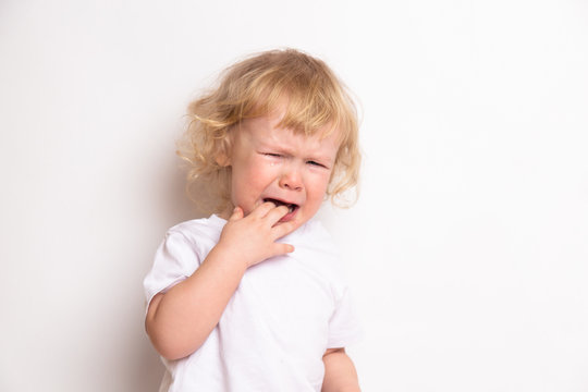 beautiful curly blond baby girl in in white t-shirt crying on a white background. the child has teeth. concept of child care illness. copy space