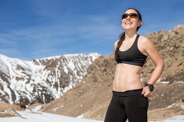 Portrait of strong hiker woman smiling in a sunny day mountains background