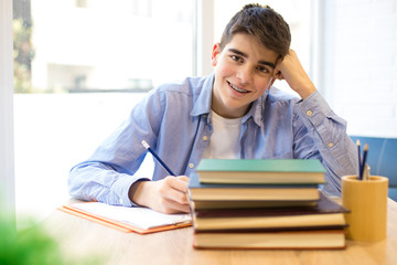 teen smiling student on the desk with books