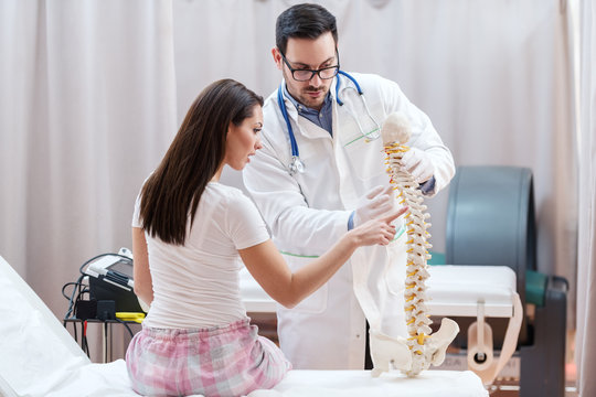 Female patient sitting with backs turned showing on spine model where she feel pain. Doctor holding spine model.