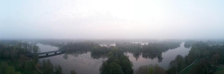 Bäume spiegeln sich im See bei Nebel Luftbildaufnahme