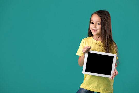 cute little child girl holding tablet with blank screen isolated on blue background