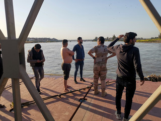 Iraqi rescuers search for survivors over the site where an overloaded ferry sank in the Tigris river near Mosul