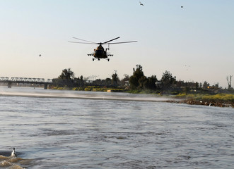 An Iraqi rescue helicopter searches for survivors over the site where an overloaded ferry sank in the Tigris river near Mosul