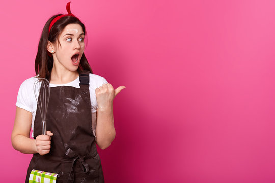 Surprised dark haired woman makes gesture with her thumb. Gifted active baker holds kitchen equipment in right hand, opens her mouth and big eyes widely, wears work clothing. Cooking concept.