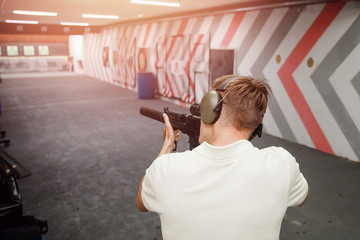 Man shoots pistol in noise protection headphones. Shooting range gun