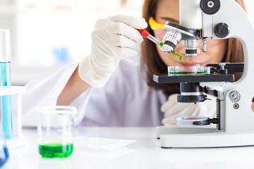 Scientist dropping liquid to petri dish..