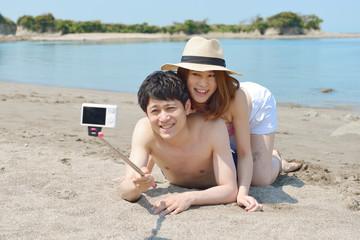 ビーチで自撮りするカップル