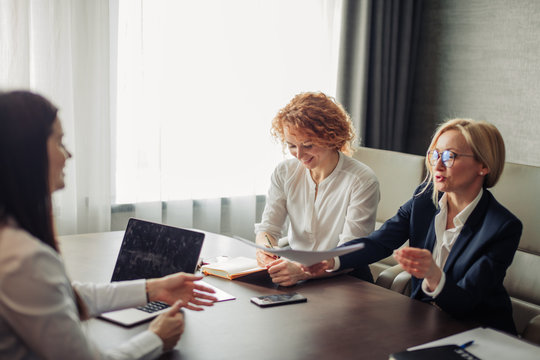Woman job applicant having an interview with two female corporate experts at office of big company. Two young beautiful women, conducting a job interview reading the female candidate s CV.