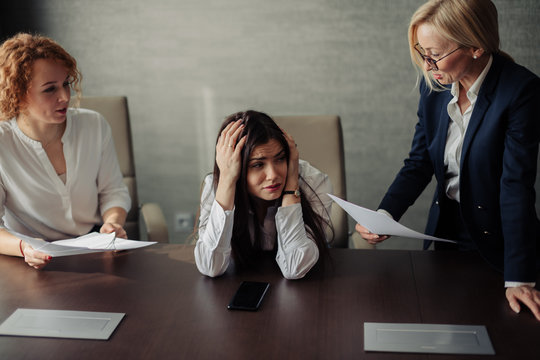 Young female office manager unable to cope with too many tasks from her boss and supervisor, suffering stress, pressing her head with desperate expression.