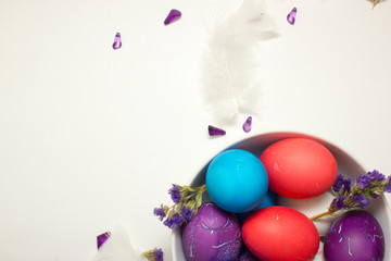 Top shot of Happy Easter decoration with colored chicken eggs in bowl on white background with free space for text