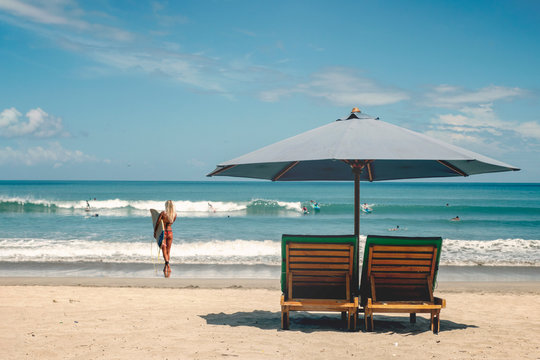 Beach umbrella with deck chairs against the ocean with surfers
