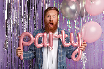 Shocked redhead well dressed man with thick bristle, holds alphabet balloons, shocked to have spoiled party with bad organization and music, makes photo against tinsel curtain. Holiday concept