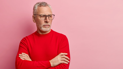 Retired bearded old man keeps arms folded, focused away with pensive look, wears spectacles and red jumper, stands over pink background, free space for your advertisement. People, age, thoughts