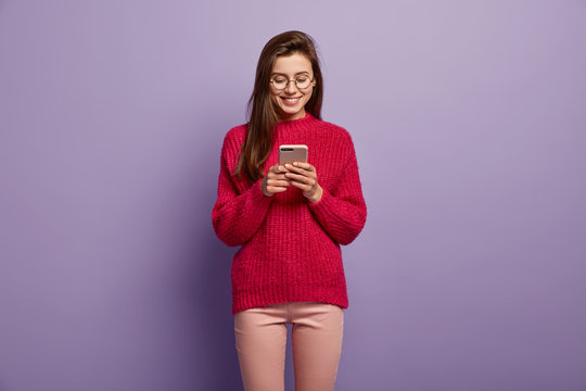 Photo of smiling Caucasian teenage girl focused in modern cell phone, enjoys online communication, wears long knitted red sweater, sends text messages to friend, stands over purple background