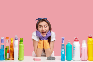 Glad female janitor keeps hands under chin, looks happily away, wears headband and casual t shirt, uses detergents and sponges for cleaning, isolated over pink background. Household concept.
