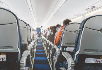 Aircraft cabin after take off. inside the plane. passengers sit on the seat in the cabin ECOM class in Boeing. the passage between the seats. economy class. Wall mural