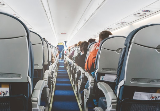 Aircraft cabin after take off. inside the plane. passengers sit on the seat in the cabin ECOM class in Boeing. the passage between the seats. economy class.