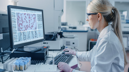 Female Scientist Sits at His Workplace in Laboratory, Uses Personal Computer. Screen Shows Analyze of DNA. I the Background Genetics Research Centre with Innovative Equipment.