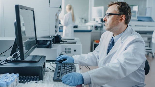 Male Research Scientist Sits at His Workplace in Laboratory, Uses Personal Computer. I the Background Genetics, Pharmaceutical Research Centre with Innovative Equipment.