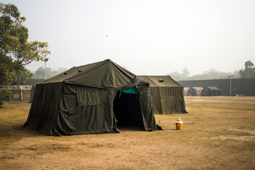 Military tent in the field. big tent city. field camp in nature. military base with temporary barracks. military exercises of the soldiers. large military tent. Army camp. reconstruction warfare.