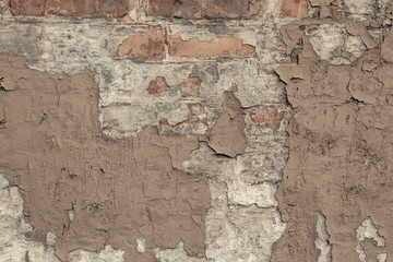 Peeling beige paint on a brick wall in vintage style. Vintage house facade. Empty space. Grunge background. old wall cement background. Light-brown shabby concrete wall texture.