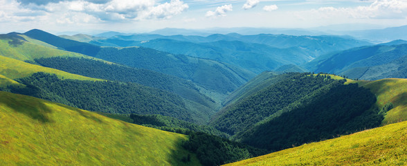 panorama of rolling hills of the ridge in summer. valley down below. grassy alpine slopes. sunny weather