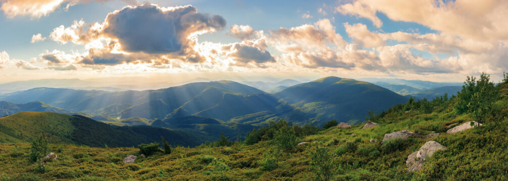 panorama of a gorgeous summer sunset in mountains. sun behind the fluffy clouds. rocks among grassy hills.