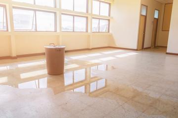 water leak drop interior office building in red bucket from Ceiling and flow on terrazzo floor