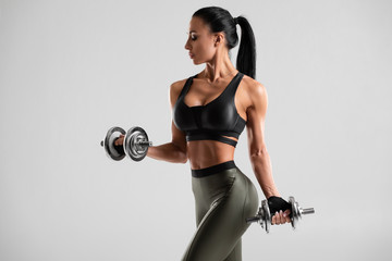 Fitness woman doing exercise for biceps on gray background. Muscular woman workout with dumbbells Wall mural