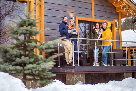 Friends stand on the veranda of a winter cottage. A group of friends rent a cottage at Christmas. Christmas weekend buddies.  Rent a cottage for holidays. Rent a vacation home with friends.